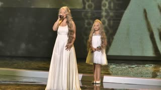 Two sisters enter the stage at a concert. Their performance will take your breath away. - Video