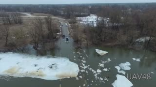 Tractor Clears Ice Floes From A Flooded Bridge - Video