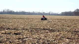 A kid in red rides a four wheeler on an open field and flips forward