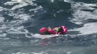 Woman in pink flower floatie crashes with waves - Video