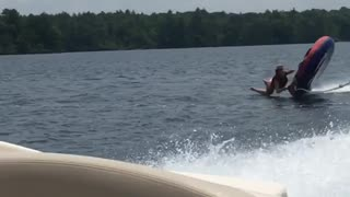 Girl flies off water tube behind boat