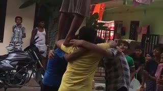 Kids banding together to lift friend in pink shirt to take down and break pinata - Video
