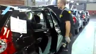 Car assembly worker makes final tweaks to the doors - Video