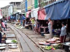 Train Passes Through Busy Market in Bangkok