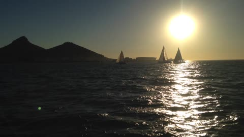 Sunset shot of three sailboats crossing the frame
