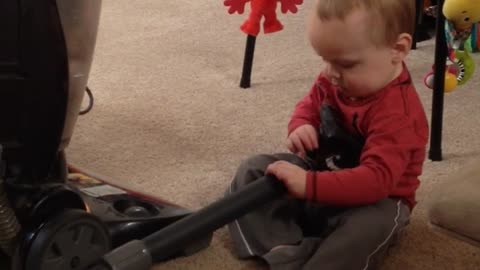 Adorable Baby Entertained By Vacuum Cleaner